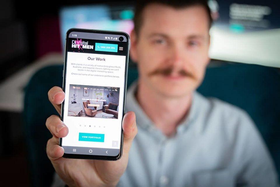 digital hitmen holding mobile phone with website